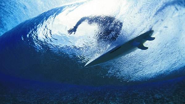 波の上のサーフボードを裏側から撮影した写真壁紙画像