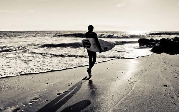 サーフボードを持って波打ち際を歩くサーファーのモノクロ写真