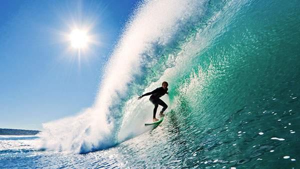 エメラルドグリーンの波と太陽が爽快なサーフィンの写真