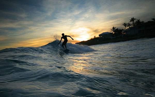 夕日の中をサーフィンする男性のシルエットの写真壁紙