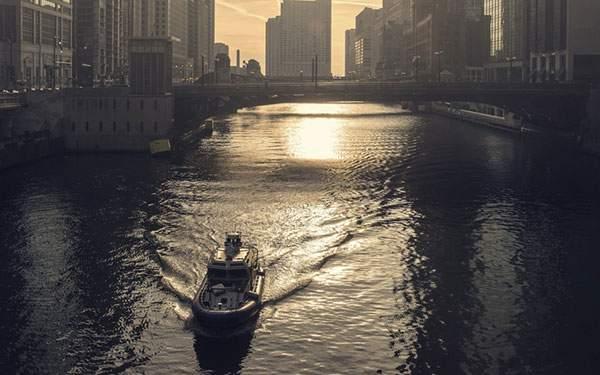 都会の橋とその下をくぐるボートの綺麗な写真壁紙画像
