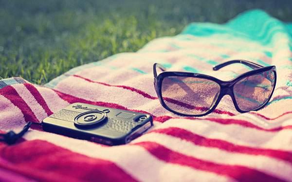 シートの上に無造作に置かれたサングラスとスマートフォンの写真画像
