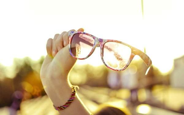 手に持ったカラフルなサングラスを逆光で撮影した綺麗な写真壁紙