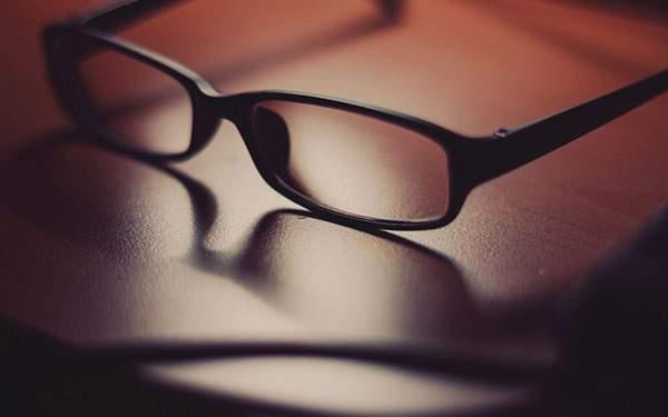机の上の黒縁メガネを撮影したクールな写真画像