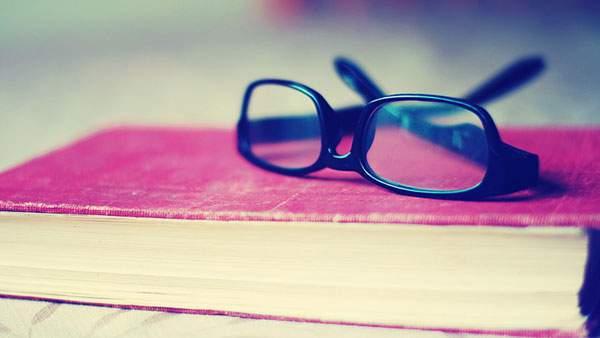 本とメガネをレトロ調の色合いで撮影したオシャレな写真画像