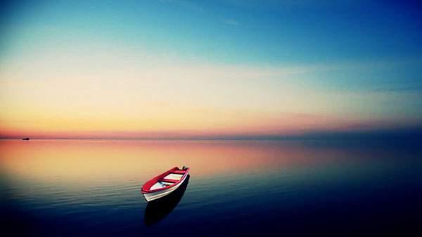赤と青の美しいグラデーションに染まった水平線とボートの写真壁紙