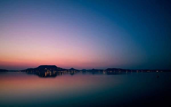 海の向こうの山と街並みを撮影した夕日の写真壁紙