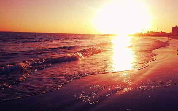 夕日の沈む波打ち際の無料壁紙画像