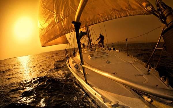 夕日に染まった海を突き進む船の写真壁紙