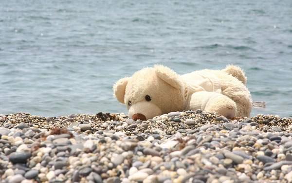 海辺の砂利の上に寝てるテディベアの爽やかな写真画像