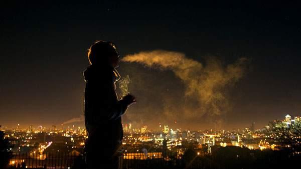 夜景をバックにタバコを吸う男性のシルエットを撮影した綺麗な写真壁紙