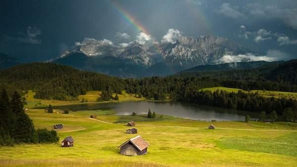 大草原の中の家と湖のむこうに出来た虹を撮影した爽やかな写真壁紙画像