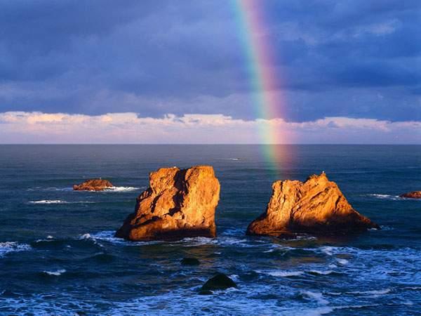 海面から顔を出した二つの岩に向かって伸びる虹の写真壁紙画像