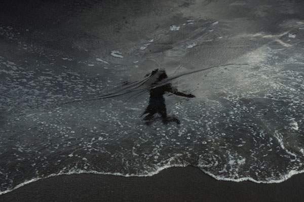 水面の反射を使ってビーチの人影を切り取った写真作品シリーズ - 02