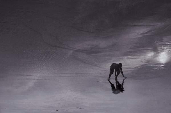 水面の反射を使ってビーチの人影を切り取った写真作品シリーズ - 04