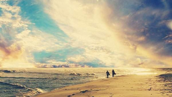 浜辺を歩く二人のシルエットを撮影した美しい写真壁紙画像