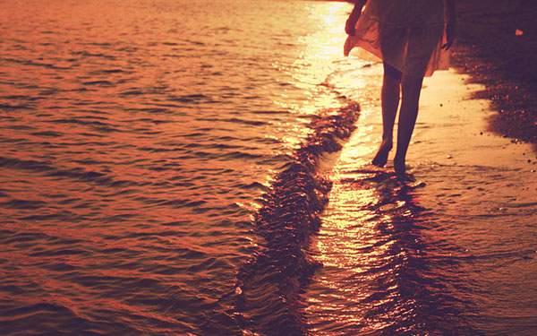夕日のに染まった波打ち際を歩く女性の足元を撮影した写真壁紙