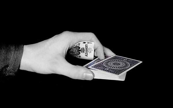 手の中にスペードのエースを隠しながらカードを配る手の写真壁紙画像