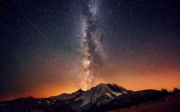 雪山の上に広がる満点の星空と流れ星の美しい写真壁紙画像
