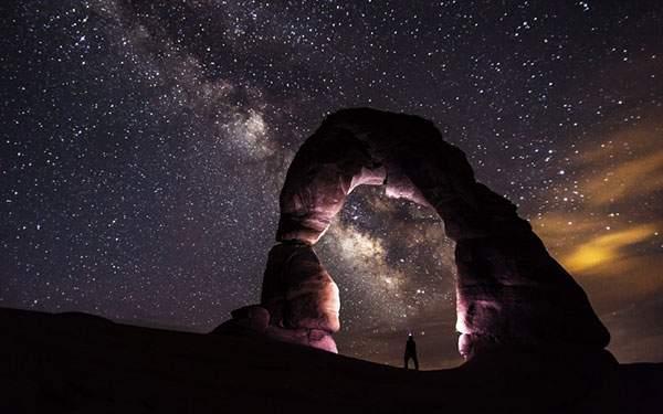 アーチ状の岩の中に立つ人のシルエットと星空の綺麗な写真壁紙画像