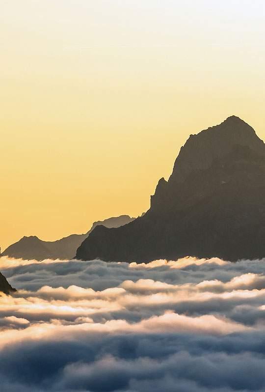 雲の上の岩山とそれを照らす夕日