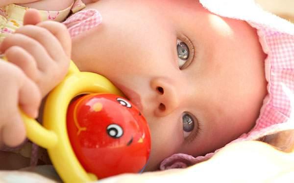 おもちゃを口にくわえた綺麗な青い目をした赤ちゃんの写真壁紙画像