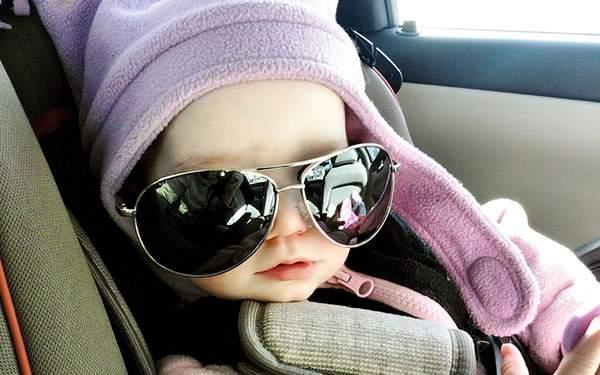大きなサングラスをしてベビーシートに座る赤ちゃんの可愛い写真壁紙画像