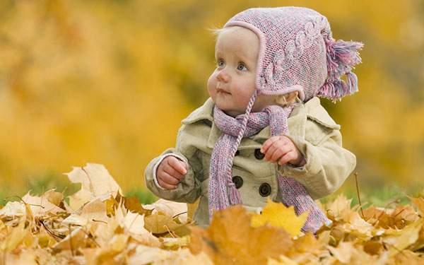 黄色い落ち葉の上に座り込んで楽しそうな赤ちゃんを撮影した可愛い写真壁紙画像