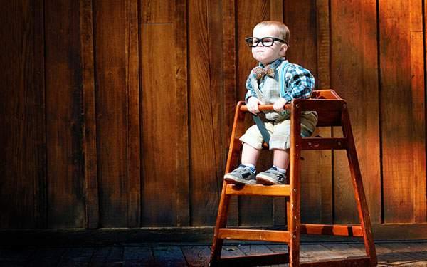 黒縁メガネをかけて椅子に座った知的な雰囲気の赤ちゃんの写真壁紙画像