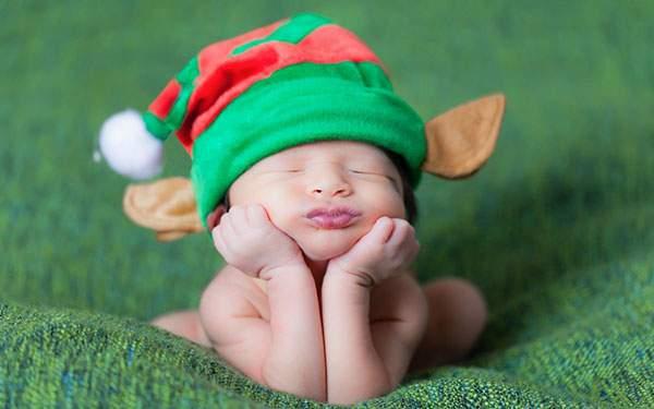 エルフの帽子を被って頬杖をつく赤ちゃんの可愛い写真壁紙画像