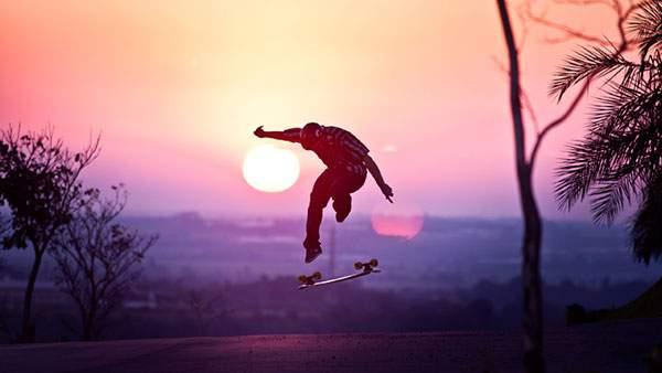夕日をバックにオーリー(ジャンプ)するスケーターの綺麗な写真壁紙画像