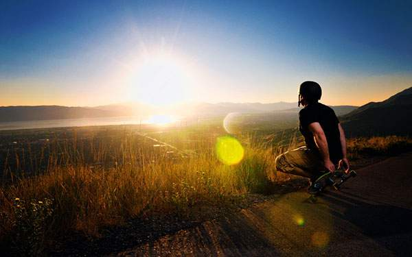 沈んでいく夕日を見つめるスケートボーダーの後ろ姿を撮影した美しい写真壁紙画像