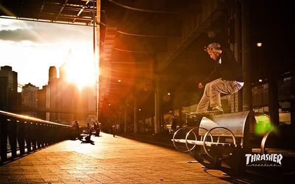 夕日に染まった街でトリックを決めるスケーターのかっこいい写真壁紙画像