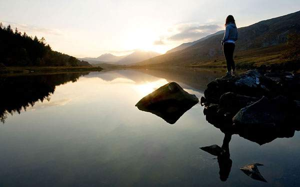 湖畔の岩に立つ女性と山の向こうから昇ってくる朝日の綺麗な写真壁紙画像