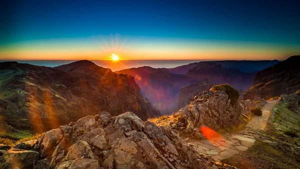 岩山の向こうから登る美しい朝日を撮影した写真壁紙画像