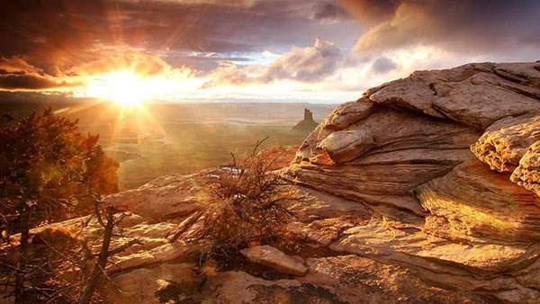 岩山と雲間から輝く朝日を撮影した綺麗な写真壁紙画像