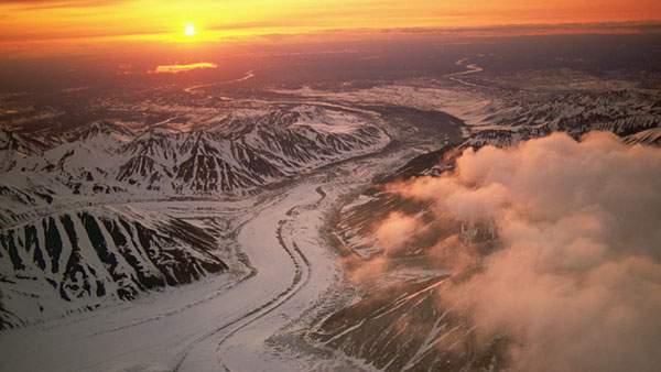 雪山と空の向こうの日の出を雲の上から撮影した写真壁紙画像