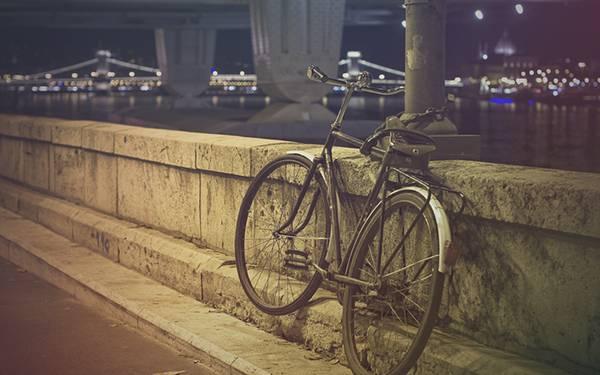 石の塀沿いの支柱にチェーンで止められた自転車のオシャレな写真壁紙画像