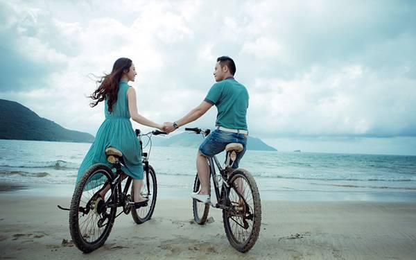 海辺で自転車に乗りながら手を ...