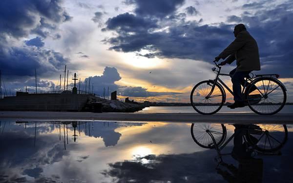自転車に乗ったおじさんと綺麗な空を反射した水たまりの美しい写真壁紙画像
