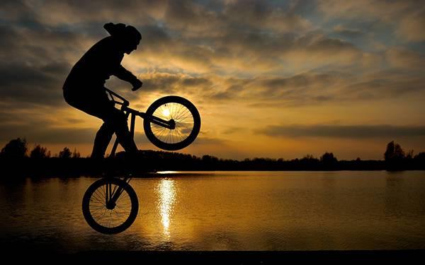 夕日をバックにウィリーをする男性のシルエットを撮影したかっこいい写真壁紙画像