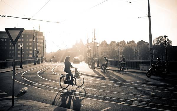 朝日の街を自転車で行き交う人々をモノクロで撮影したおしゃれな写真壁紙画像