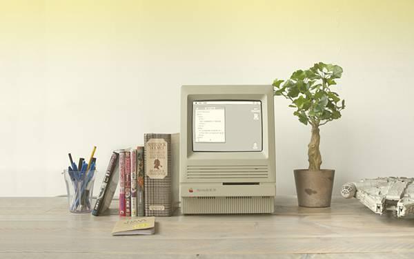机の上のコンピューターと本や観葉植物を撮影した写真壁紙画像
