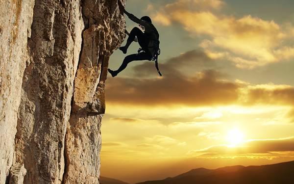 夕日をバックに断崖絶壁を素手で登るロッククライマーの写真壁紙画像