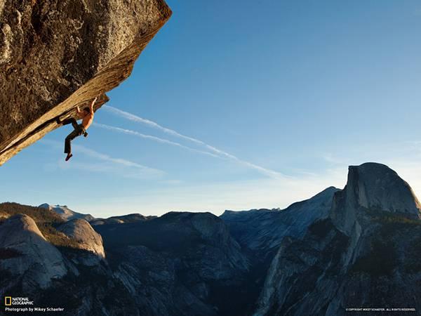 オーバーハングの岩肌を登っていくクライマーのかっこいい写真壁紙画像