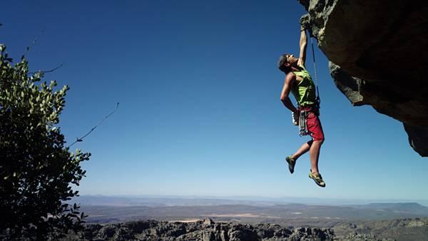 岩に掴まって片手で体重を支えるクライマーを撮影した写真壁紙画像