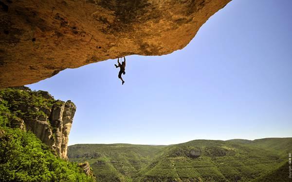 ひさしのように突き出した岩肌に掴まったロッククライマーの写真壁紙画像