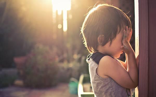 06.夕日の中で両手で顔をおさえる男の子を撮影した綺麗な写真壁紙画像