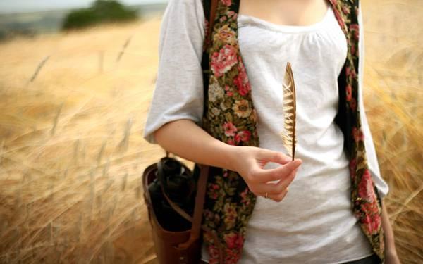 04.羽を持って歩く女性の手元を撮影した写真壁紙画像