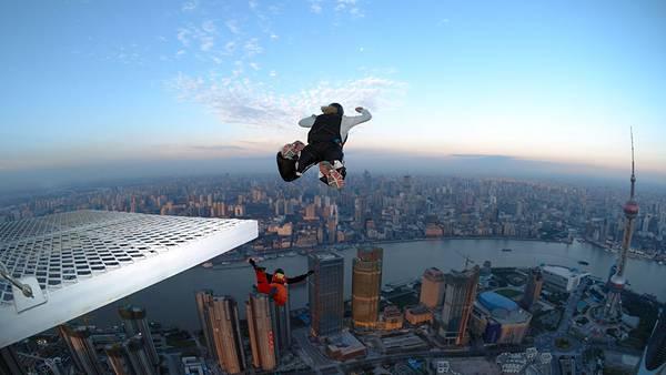 08.高層ビルの立ち並ぶ街でベースジャンプする男性の写真壁紙画像